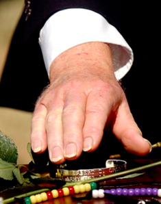 POW/MIA bracelet placed on coffin at graveside by comrade.